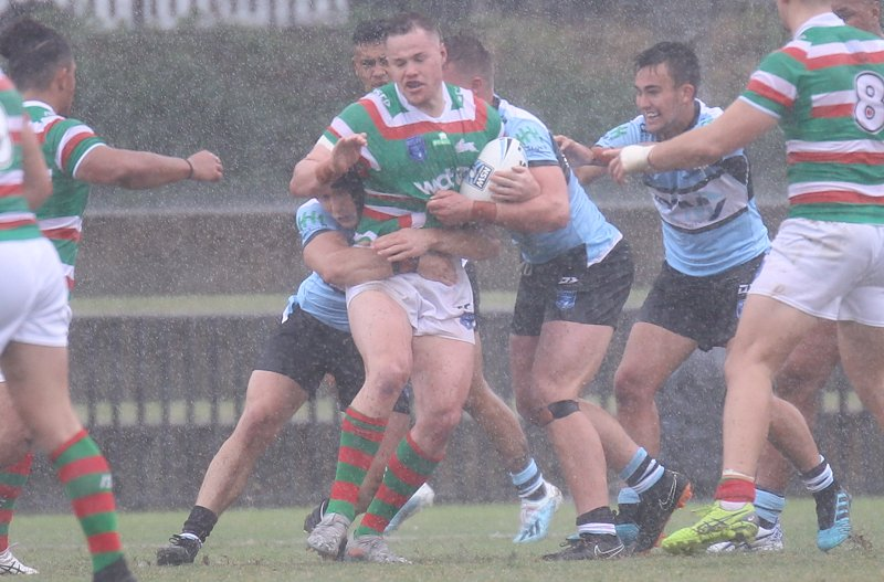 Luke Bain Rabbitoh's Lock get wrapped up by the Sharks Defense in the massive downpour at Redfern Oval on Sunday in the NSWRL Jersey Flegg Cup Season opener (Photo : Steve Montgomery)